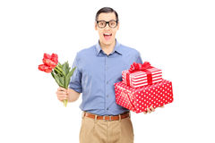 Man holding flowers and presents Stock Photo