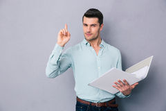 Man holding folder and pointing finger up Stock Photo