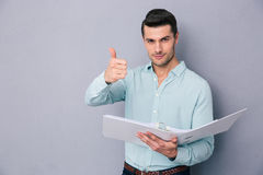 Man holding folder and showing thumb up Stock Images