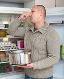 Man holding foul food near fridge. Man holding his nose because of bad smell near fridge at home stock images