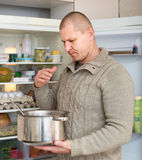 Man holding foul food near fridge. Man holding nose because of bad smell near fridge at home royalty free stock photography