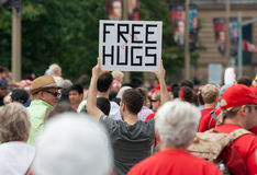 Man Holding Free Hugs Sign in Crowd Stock Photo