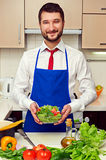 Man holding fresh salad and looking at camera Royalty Free Stock Photo