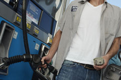 Man Holding Fuel Pump And Money Stock Photography