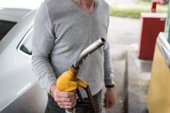 Man holding a fuel pump nozzle Stock Images