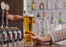 Man holding a full pint glass of beer. Man sitting at a counter in the bar holding a full pint glass of beer, close up view of his hand with the taps for stock photo