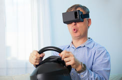 Man holding a gaming computer wheel getting experience using VR-headset glasses Royalty Free Stock Photo
