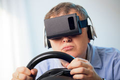 Man holding a gaming computer wheel getting experience using VR-headset glasses Royalty Free Stock Images
