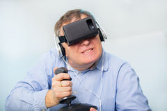 Man holding a gaming computer wheel getting experience using VR-headset glasses Stock Images