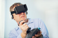 Man holding a gaming computer wheel getting experience using VR-headset glasses Stock Photography