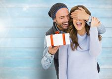 Man holding a gift box and covering eyes of woman. Happy man holding a gift box and covering eyes of woman against wooden background Royalty Free Stock Image