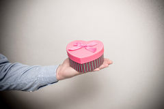 Man holding a gift box. In the form of heart Royalty Free Stock Photos