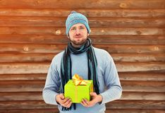 Man holding gift box in hands. Handsome unshaven man holding gift box in hands. holiday present Royalty Free Stock Photos