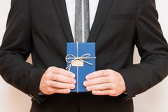 A man holding a gift box in his hands. A man in a suit holds a gift box in his hand Stock Photo