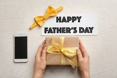 Man holding gift box near smartphone and bow tie on table. Top view. Father`s day celebration Stock Images
