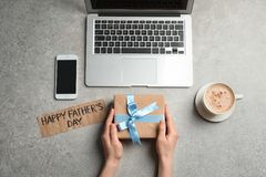 Man holding gift box near smartphone. And laptop on table, top view. Father`s day celebration Royalty Free Stock Photos