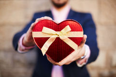 Man holding gift in the form of heart Stock Images
