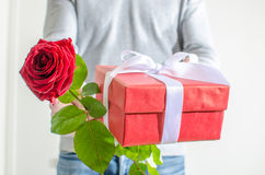 Man holding a gift and a red rose Royalty Free Stock Photo