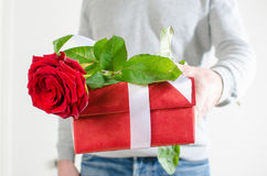 Man holding a gift and a red rose Stock Photography