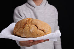 Man holding or giving bread as a welcome. Baker offer loaf of tasty fresh bread Royalty Free Stock Photos