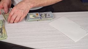 Man holding and giving cash to someone on old wooden table ,business concept. Money US bank note. stock video footage