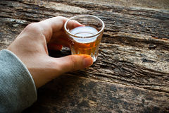 Man holding a glass of alcohol on table Stock Images