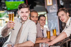 Man holding a glass of beer in hand while sitting at the bar and Stock Image
