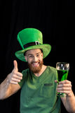 Man holding glass of beer on St.Patrick`s day and showing thumb up on black Stock Image