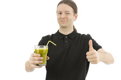 Man holding a glass of green smoothie and giving thumbs up Stock Photos