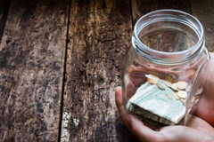 Man holding a glass jar for donations box Stock Photos