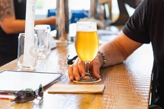Man Holding Glass of Micro Brew Beer at Bar. Man Holding Glass of Micro Brew Beer at a Bar royalty free stock photo