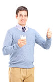 Man holding a glass of milk and giving thumb up Stock Photography