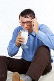 Man holding Glass of Milk. Sitting on rug Stock Images
