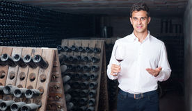 Man holding glass with wine in cellar. Portrait of smiling expert man holding glass with wine sample in cellar with bottles Stock Photos