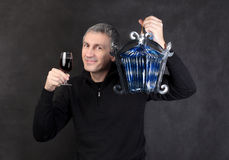 Man holding a glass wine and lantern. On gray background Royalty Free Stock Photos