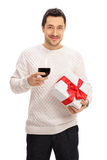 Man holding a glass of wine and a present Royalty Free Stock Image
