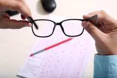 Man is holding glasses in hand. Picture of mouse, pencil and OMR sheet royalty free stock image