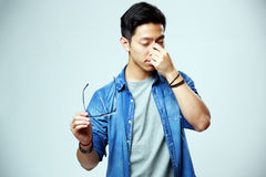 Man holding glasses and rubbing his eyes. Asian man holding glasses and rubbing his eyes on gray background Royalty Free Stock Photo