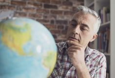 Man holding a globe and finding locations. Man holding a globe and searching locations, he is planning his vacations and an international travel stock photography