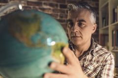 Man holding a globe and finding locations. Man holding a globe and searching locations, he is planning his vacations and an international travel stock images