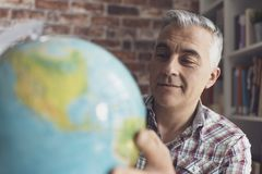 Man holding a globe and finding locations. Smiling man holding a globe and searching locations, he is planning his vacations and an international travel stock photos