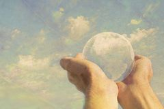 Man holding globe in hands with arms outstretched against a blue sky Stock Photos