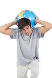 Man holding a globe on his back Royalty Free Stock Photo