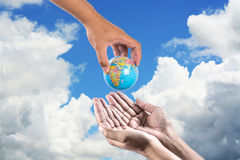 Man holding a globe in his hands. give the earth to human on sky Royalty Free Stock Photo