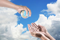 Man holding a globe in his hands. give the earth to human on sky Royalty Free Stock Images