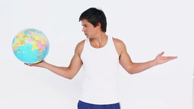 Man holding a globe in one hand and a blank space in the other one stock video