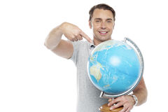 Man holding globe and pointing over it Royalty Free Stock Photography