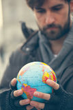 Man Holding Globe. Young Man Holding Globe Outdoors Stock Image