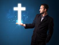 Man holding a glowing cross in his hand Royalty Free Stock Image