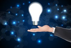 Man holding a glowing lightbulb in her hand Royalty Free Stock Photo